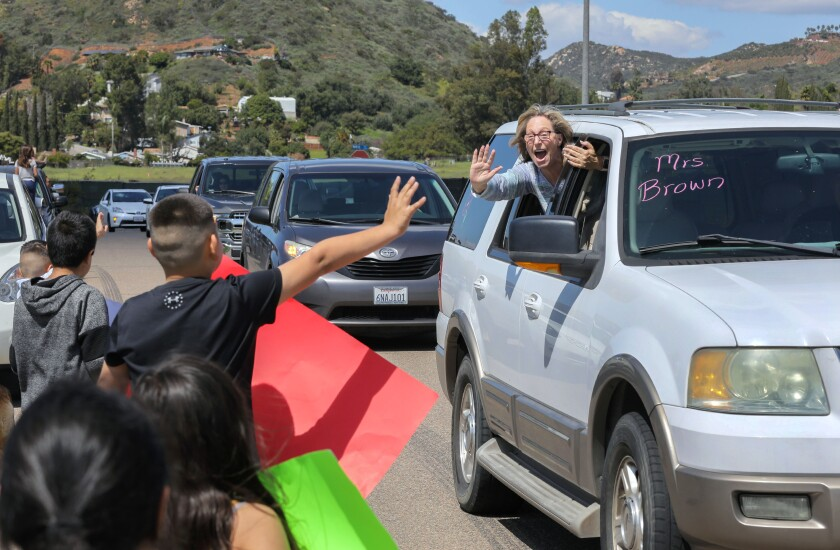 Reidy Creek Elementary School first grade teacher Desiree Brown greets students as her teacher caravan from the school passes by students and parents parked along Conway Drive, near North Avenue on Friday, March 27.