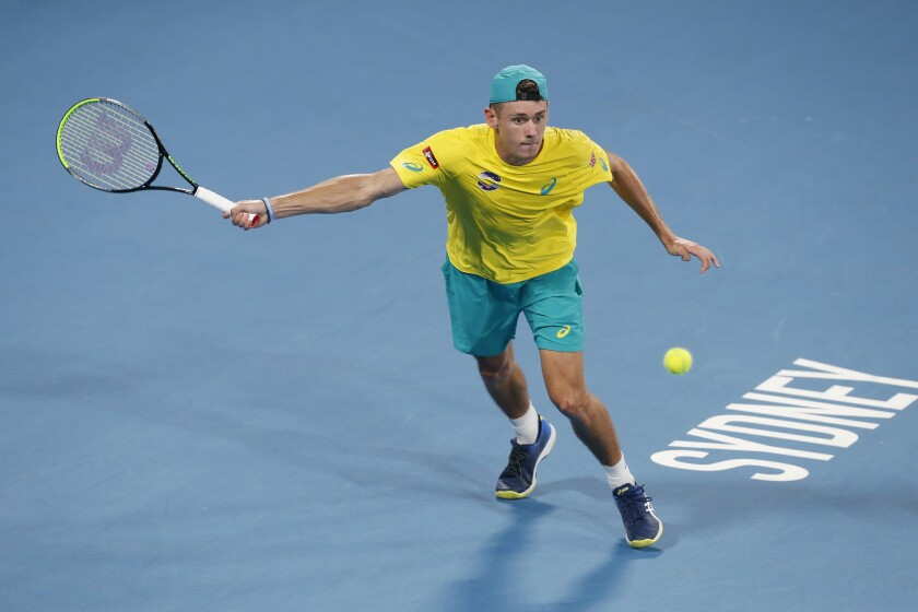 FILE - In this Jan. 11, 2020, file photo, Alex de Minaur of Australia plays a shot against Rafael Nadal of Spain during their ATP Cup tennis match in Sydney. Top-seeded Alex de Minaur was forced out of the Adelaide International Monday, Jan. 13, 2020 with an abdominal strain. (AP Photo/Steve Christo, File)