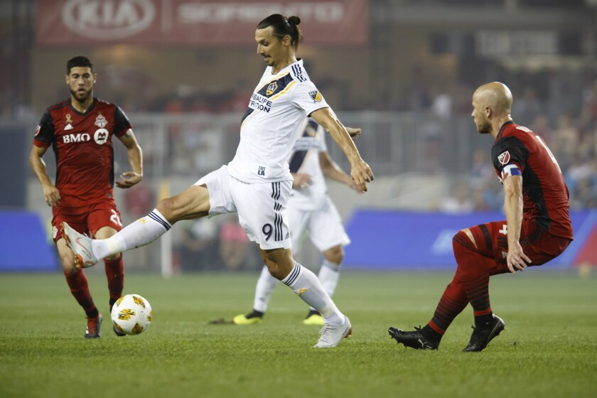Los Angeles Galaxy forward Zlatan Ibrahimovic (9) controls the ball against Toronto FC midfielder Michael Bradley (4) during the first half of an MLS soccer game, Saturday, Sept. 15, 2018 in Toronto.