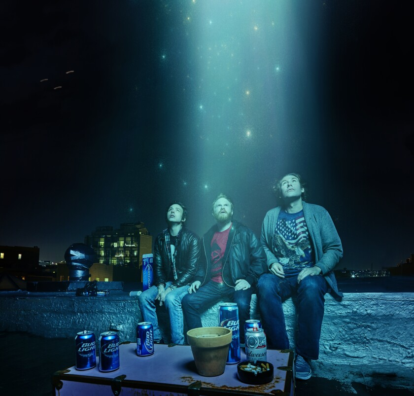 Three people look up into the sky as starlight shines down