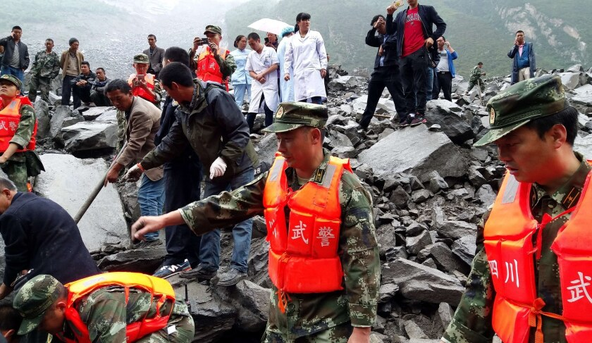 Rescuers work at the site of a massive landslide Saturday in Maoxian county, southwest China.