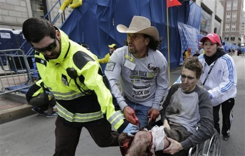 Medical responders run an injured man past the finish line the 2013 Boston Marathon following an explosion in Boston, Monday, April 15, 2013. Two explosions shattered the euphoria of the Boston Marathon finish line on Monday, sending authorities out on the course to carry off the injured while the