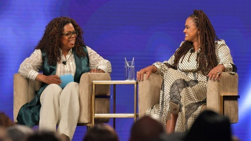 """Oprah Winfrey, left, and Ava DuVernay chat at an Emmy event for DuVernay's 2019 Netflix limited series, """"When They See Us."""""""