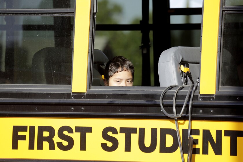 A student peers through the broken window of a school bus that was in an accident involving a Metro train crossing arm Tuesday morning at 55th Street and Long Beach Avenue in South Los Angeles.