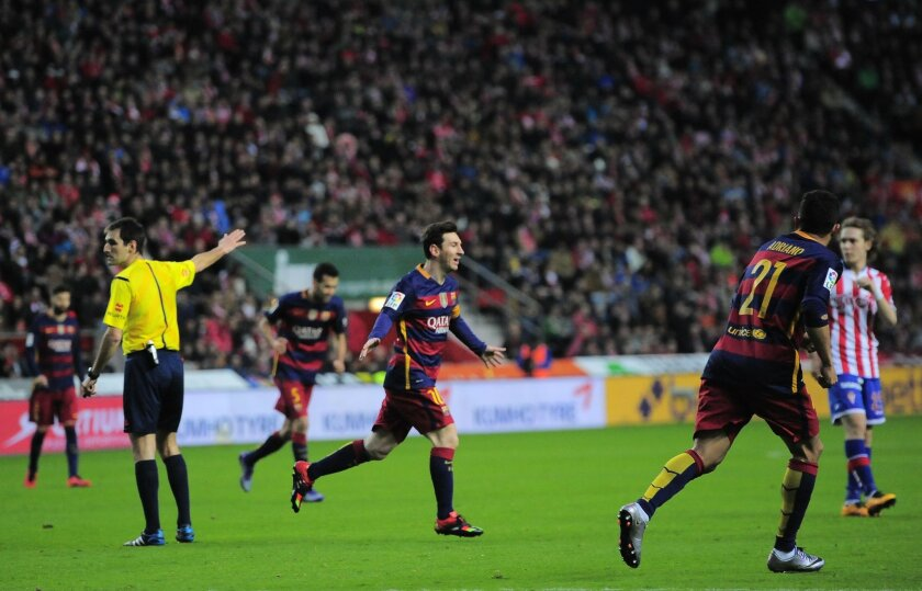 FC Barcelona's Lionel Messi of Argentina, center, celebrates his goal after scoring during their Spanish La Liga soccer match between Sporting de Gijon and FC Barcelona, at El Molinon stadium, in Gijon, northern Spain, Wednesday, Feb.17, 2016. (AP Photo/Alvaro Barrientos)