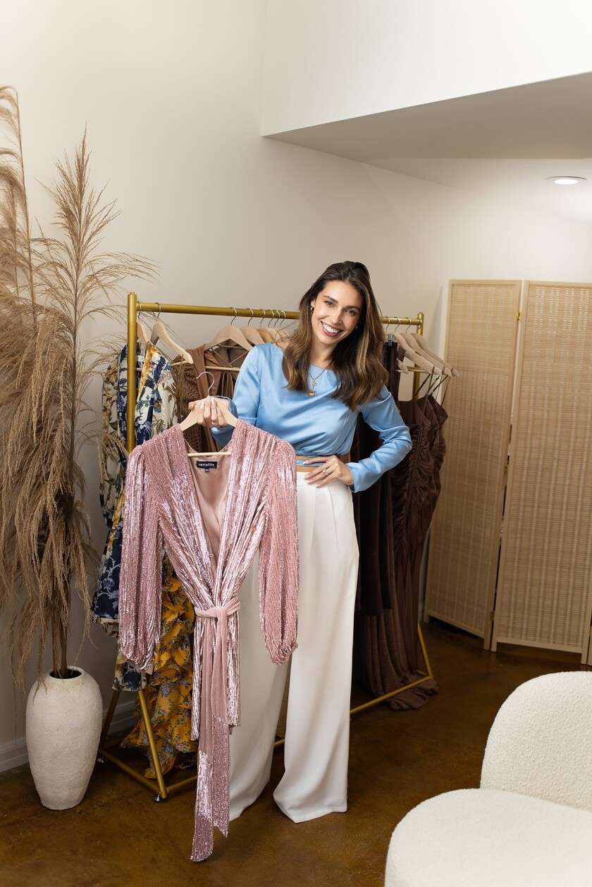 Una Notte owner and La Jolla resident Jackie Modena displays clothes in the business's Prospect Street showroom.