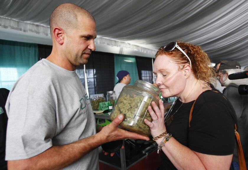 Alicia Tucker, right, smells marijuana as Robert Kirk of Duber Collective helps her out at PotLuck, a Medical Cannabis Expo. Tucker has Alpha 1-antitrypsin deficiency.