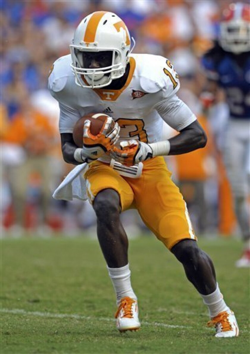FILE - In this Sept. 17, 2011, file photo, Tennessee receiver DeAnthony Arnett makes a reception during an NCAA college football game against Florida in Gainesville, Fla. Arnett asked to be released from his commitment at Tennessee so he could transfer to Michigan or Michigan State and be closer to his ailing father, who's undergone two surgeries since Arnett returned home for winter break and might need a third. Tennessee initially said it would not release Arnett to play at either Big Ten school _ meaning he would have to sit out at least a season before playing for either _ but offered to do so if Arnett chose to play at one of the Mid-American Conference schools in the state _ Central Michigan, Western Michigan or Eastern Michigan. Though school officials won't take the matter up again until Tuesday at the earliest, a spokesman for Tennessee said Monday, Jan. 2, 2012, that the decision wasn't likely to change. (AP Photo/Phelan M. Ebenhack, File)