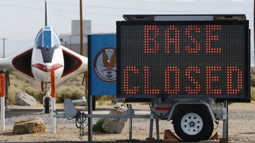 A sign announcing a base closure is posted outside the main gate to Naval Air Weapons Station China Lake on Sunday in Ridgecrest, Calif.