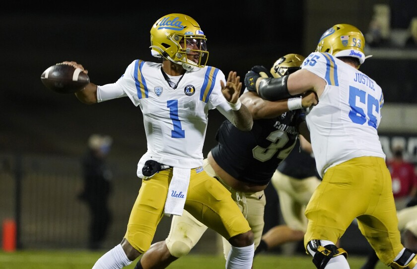 UCLA's Paul Grattan Jr. blocks Colorado's Mustafa Johnson as Dorian Thompson-Robinson attempts a pass.