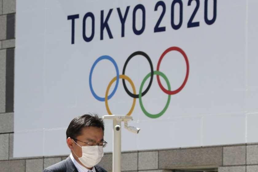 A man walks past a banner of an Olympics logo in Tokyo on March 25.