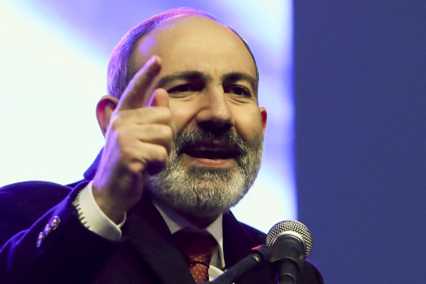 Armenian Prime Minister Nikol Pashinyan gestures while addressing his supporters during a rally in his support in the center of Yerevan, Armenia, Monday, March 1, 2021. Amid escalating political tensions in Armenia, supporters of the country's embattled prime minister and the opposition are staging massive rival rallies in the capital of Yerevan. Prime Minister Nikol Pashinyan has faced opposition demands to resign since he signed a peace deal in November that ended six weeks of intense fighting with Azerbaijan over the Nagorno-Karabakh region. (Hayk Baghdasaryan/PHOTOLURE via AP)