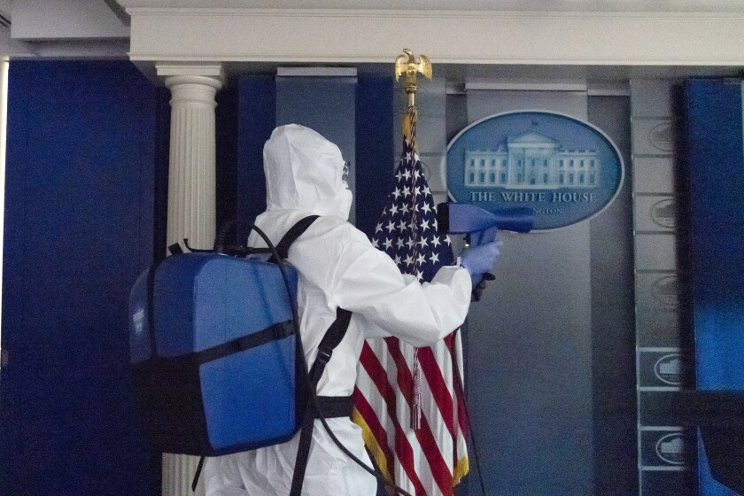 A member of the cleaning staff sprays The James Brady Briefing Room of the White House, Monday, Oct. 5, 2020, in Washington. (AP Photo/Alex Brandon)