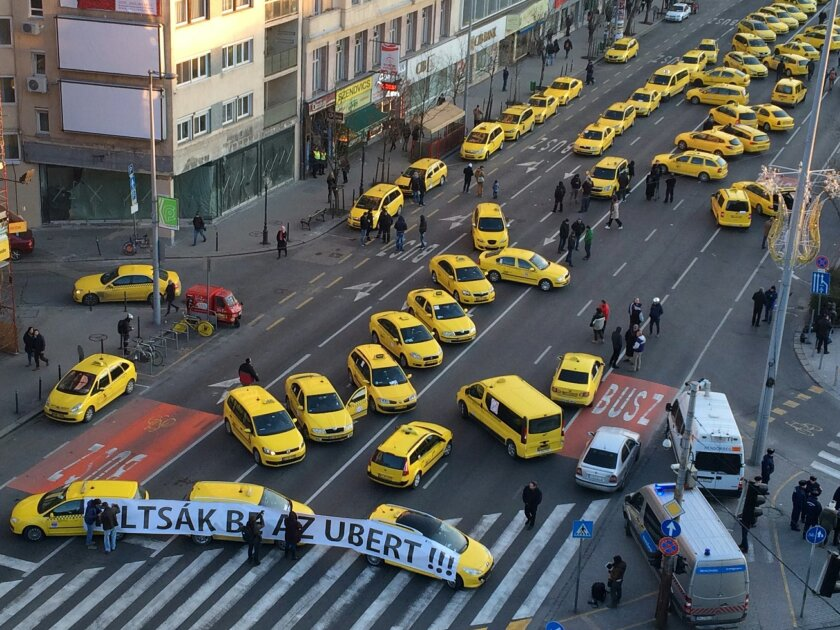 "Budapest taxis drivers block traffic as they protest demanding a ban on Uber in downtown Budapest, Hungary, Jan. 18, 2018. More than 100 taxis blocked traffic in downtown Budapest as drivers demanded a ban on Uber and other ride-hailing apps. The yellow vehicles from several taxi companies blocked off a key intersection near St. Stephen's Basilica in the Hungarian capital, causing significant traffic delays. Banner reads in Hungarian: ""Ban Uber!"" (AP Photo/Bela Szandelszky)"