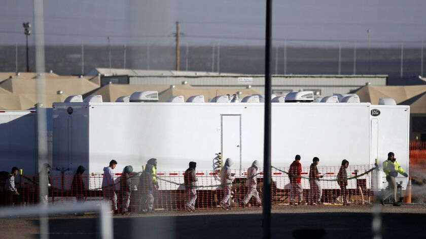 Migrant teens walk in a line through the Tornillo detention camp in Tornillo, Texas, Thursday, Dec.