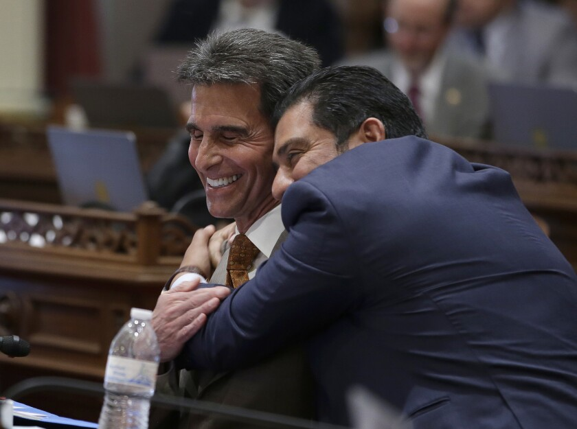 State Sen. Mark Leno (D-San Francisco) left, one of the authors of a bill to raise California's minimum wage, is hugged by Sen. Ben Hueso (D-San Diego) during the Senate vote on the bill.