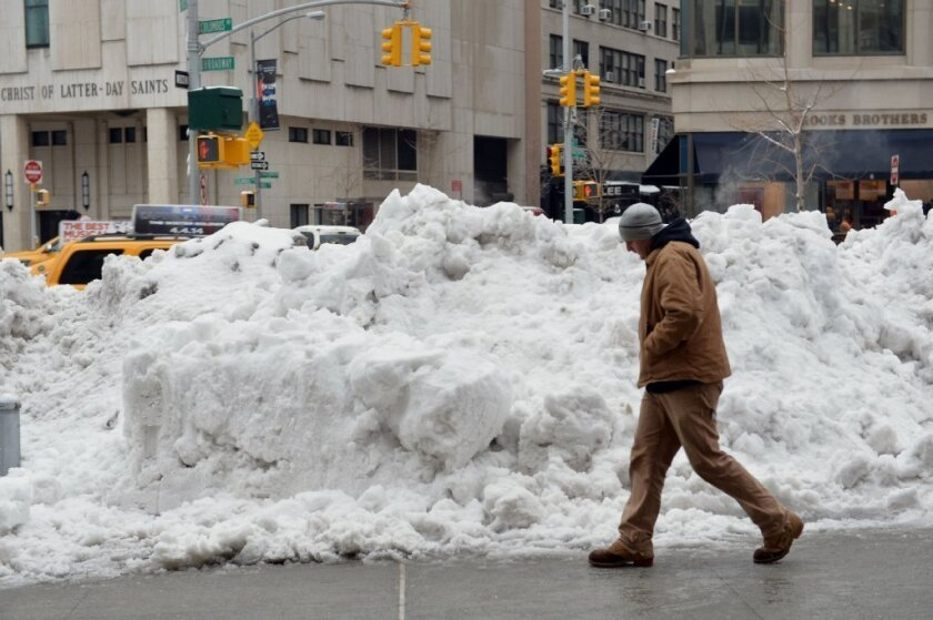 A man walks past a pile of snow in Manhattan after the latest storm dropped more snow on the Northeast and caused a buildup of ice. Some areas reported salt shortages because of the unusually snowy winter.