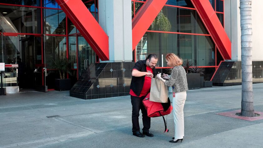 DoorDash courier Sergio Reyes, left, looks through an order before giving it to Mary-Sara Jones in downtown San Diego. The food delivery app is expanding outside of San Diego proper and into more suburban parts of the county.