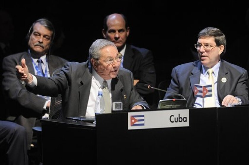 In this photo released by the CELAC Prensa Cumbre, Cuba's President Raul Castro, front left, speaks during the CELAC summit as his Foreign Minister Bruno Rodriguez Parrilla, right, looks on in Santiago, Chile, Monday, Jan. 28, 2013. Castro took over the rotating presidency of the Community of Latin American and Caribbean States on Monday in what he says is a show of regional unity against U.S. efforts to isolate the communist government through a 50-year-old economic embargo. (AP Photo/CELAC, Prensa Cumbre)