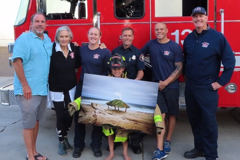 WORTH A THOUSAND 'THANK YOUS': Members of Fire Station 13 accept a photo of The Shack donated by the Windansea Surf Club earlier this month. The donation was made to thank the station for assisting during its Chloe Buckley paddle-out on July 28, 2018. Pictured are photographer Mark Bromley, community activist Melinda Merryweather, firefighters Monica Switick, Daran Osborne, Michael Silva and Donnie Everson, and Cortez Jernigan holding the photo.