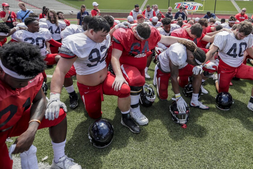 Liberty University football players kneel in prayer following an intrasquad scrimmage at Williams Stadium.