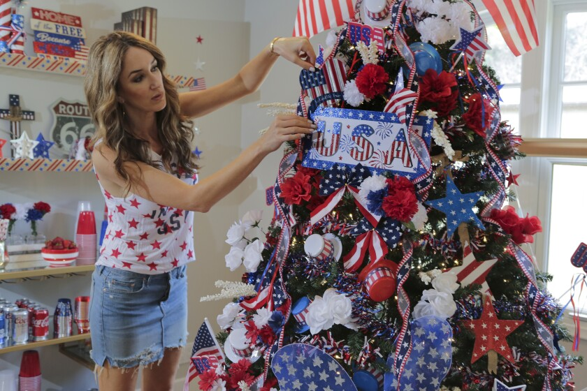 Nadia Colucci decorates the year-round Christmas tree in her Encinitas home in honor of the Fourth of July.