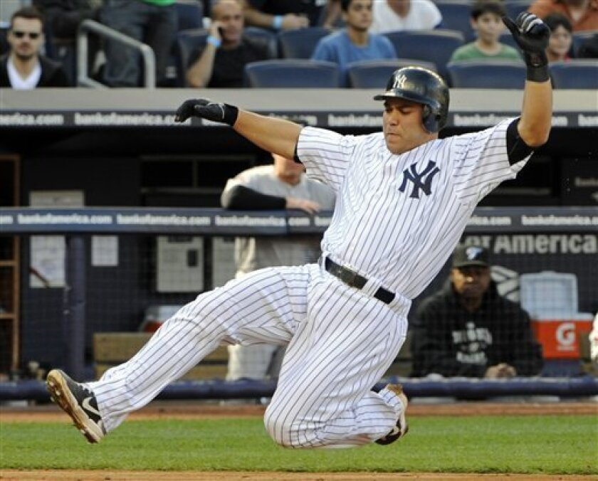 New York Yankees' Russell Martin scores on a single by Curtis Granderson during the second inning of a baseball game against the Toronto Blue Jays, Saturday, April 30, 2011, at Yankee Stadium in New York. (AP Photo/Bill Kostroun)
