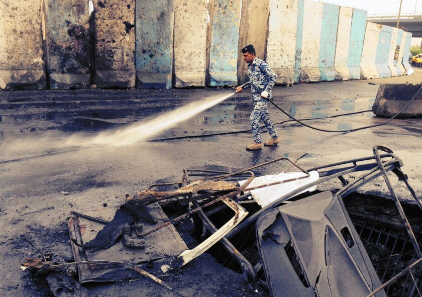 An Iraqi police officer cleans up blood and debris after a car bombing in Baghdad. Seventeen vehicles were incinerated in the deadly attack.