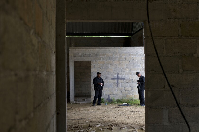 State police stand inside a warehouse where a black cross covers a wall near blood stains on the ground in Tlatlaya, Mexico. The army initially said 22 people were killed on June 30 in a gun battle between soldiers and an armed gang. But journalists found evidence that suggested a one-by-one killing of gang members.