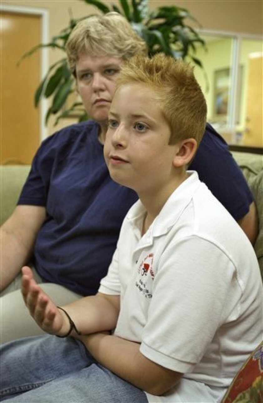 Eleven-year-old Zach Bonner answers a question as his mother Laurie looks on Monday afternoon May 4, 2009 in Seffner, Fla. Bonner is getting ready to finish his hike from Tampa to Washington to draw attention to homelessness among children. The boy pledged to walk from his home near Tampa all the way to Washington to raise money and awareness of the cause and finished the Tampa-to-Tallahassee leg in 2007, then walked from Tallahassee to Atlanta last year. On Monday, Zach will embark on the final leg, 668 miles from Atlanta to Washington. (AP Photo/Chris O'Meara)