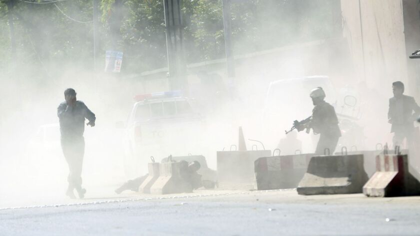 Security forces stand amid smoke at the site of a suicide attack after the second bombing in Kabul,