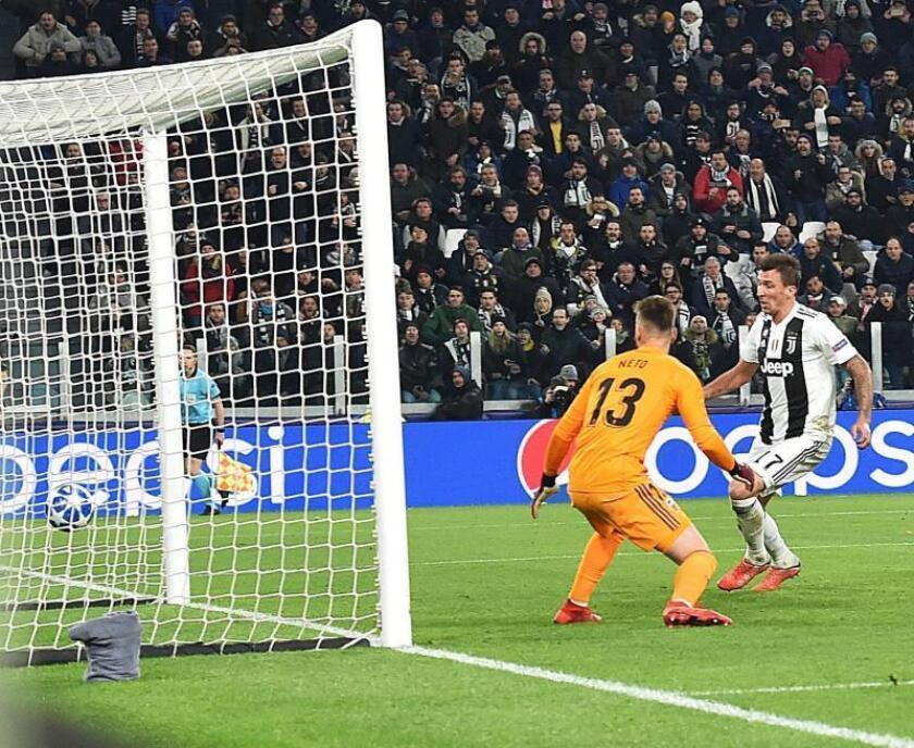 Mario Mandzukic (d) de la Juventus anota un gol ante el Valencia durante el partido de fútbol del Grupo H de la Liga de Campeones de la UEFA, entre el Juventus FC italiano y el Valencia CF español, en el estadio Allianz de Turín (Italia). EFE