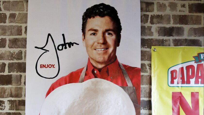FILE- In this Dec. 21, 2017, file photo shows signs, including one featuring Papa John's founder Joh