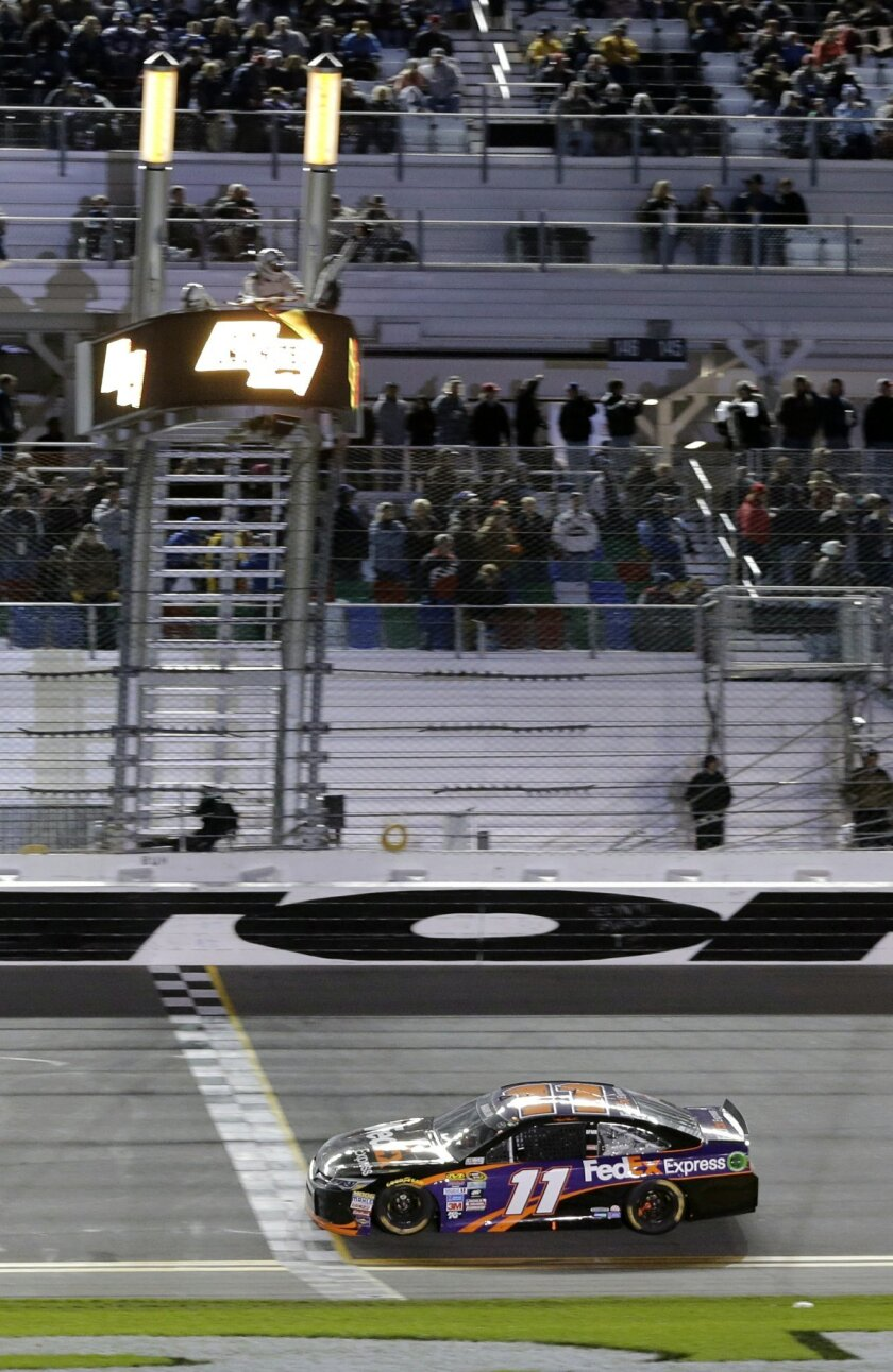 Denny Hamlin crosses the finish line to win the Sprint Unlimited auto race at Daytona International Speedway, Saturday, Feb. 13, 2016, in Daytona Beach, Fla. (AP Photo/Terry Renna)