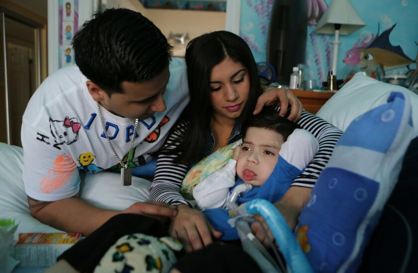 """Parents Jacob Wallis and Lucy Verde tend to """"Baby Izaiah"""" at their home in Vista in December 2013. A teen drunk driver hit Izaiah, who was riding in a stroller pushed by his grandfather in 2010. Izaiah is permanently disabled."""