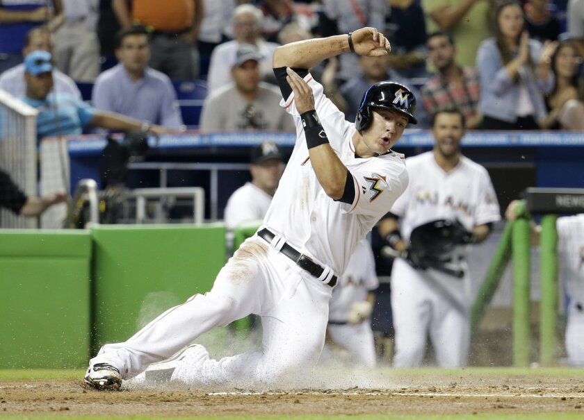 Miami Marlins' Derek Dietrich scores on a double hit by Casey McGehee in the first inning of a baseball game against the Atlanta Braves, Thursday, May 1, 2014, in Miami. (AP Photo/Lynne Sladky)