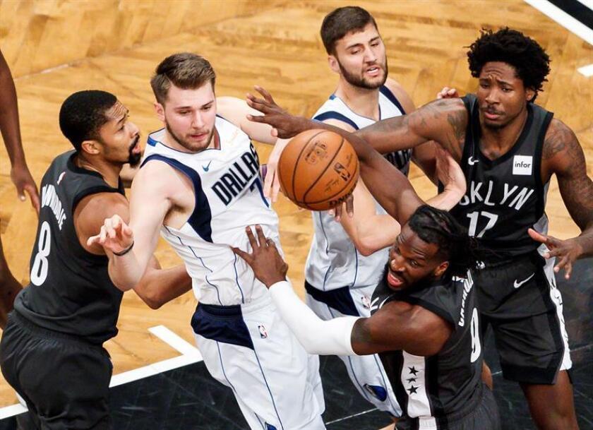 Spencer Dinwiddie (i) y DeMarre Carroll (2-d) de Nets disputan un balón con Luka Doncic (2i) de Mavericks este lunes en un partido de la NBA entre Dallas Mavericks y Brooklyn Nets, en Barclays Center en Brooklyn, Nueva York (EE.UU.). EFE