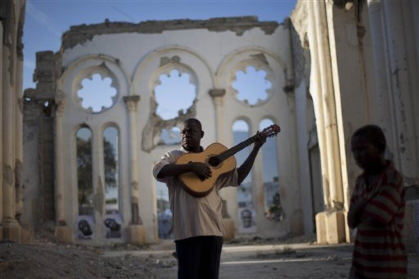 A man plays a guitar in the earthquake damaged Cathedral as people visit different areas of the city where people were killed during the Jan. 2010 earthquake in Port-au-Prince, Haiti, Thursday Jan. 12, 2012. Haitians are marking the second anniversary of the devastating 2010 earthquake which according to government officials killed 316,000 people and displaced 1.5 million. More than 500,000 are still in temporary settlement camps. (AP Photo/Ramon Espinosa)