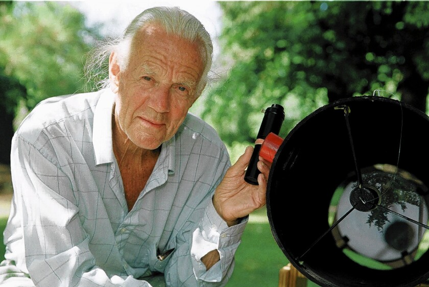 John Dobson poses with one of his homemade telescopes in Monmouth, Ore. The former monk decades ago revolutionized amateur astronomy with a design for a cheap but powerful telescope, eventually embraced by commercial manufacturers. He never patented it, being philosophically opposed.