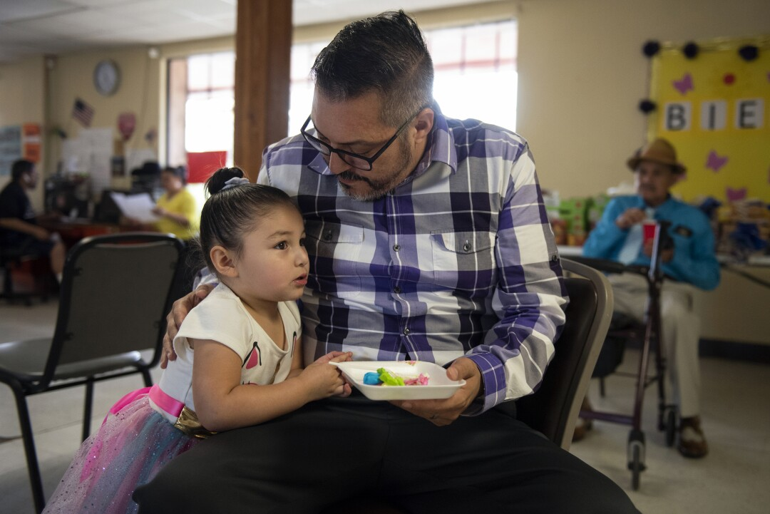Mike Smith eats cake with his daughter, Eva, 3, after a service at the Holding Institute, a community center he oversees.