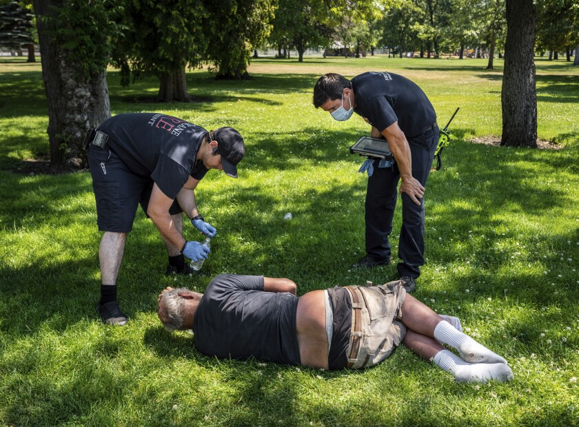 FILE — In this June 29, 2021 file photo, with temperatures well over 100 degrees, Spokane, Wash., firefighter Sean Condon, left and Lt. Gabe Mills, assigned to the Alternative Response Unit of of Station 1, check on the welfare of a man in Mission Park in Spokane, Wash.. The special fire unit, which responds to low priority calls, has been kept busy during this week's heatwave. (Colin Mulvany/The Spokesman-Review via AP, File)