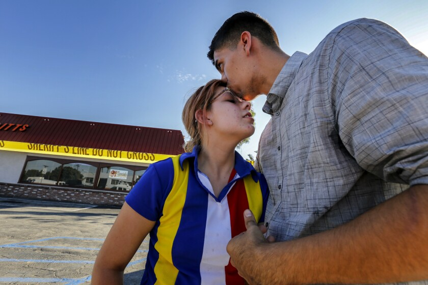 High school sweethearts, Madelynn Bastidas, left, and Oscar Madriles, hug each other in front a Downey barbecue restaurant where they were dining when a gunman ran in and took hostages.