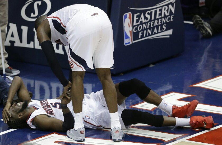 Atlanta Hawks forward DeMarre Carroll lies on the court as Atlanta Hawks forward Paul Millsap (4) speaks after Carroll was injured against the Cleveland Cavaliers during the second half in Game 1 of the Eastern Conference finals of the NBA basketball playoffs, Wednesday, May 20, 2015, in Atlanta. (AP Photo/David Goldman)