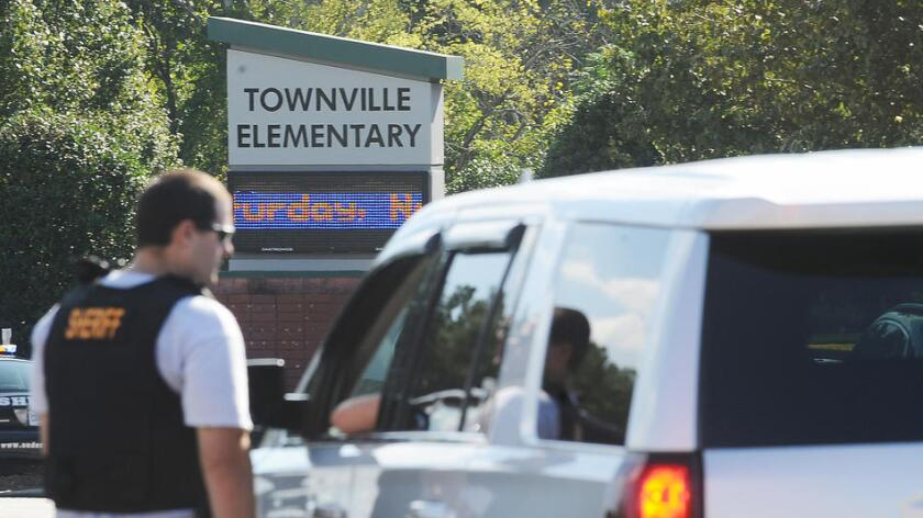Members of law enforcement talk in front of Townville Elementary School on Wednesday, Sept. 28 in Townville, S.C. (Rainier Ehrhardt / Associated Press)