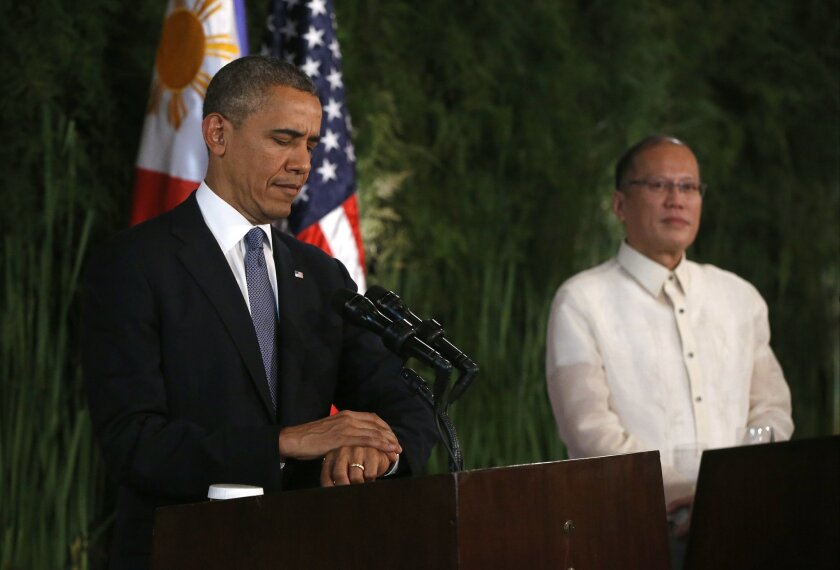 U.S. President Barack Obama looks at his watch before answering a reporter's question during a joint news conference with Philippines President Benigno Aquino III at Malacanang Palace in Manila, the Philippines, Monday, April 28, 2014. President Obama said a 10-year agreement signed Monday to give