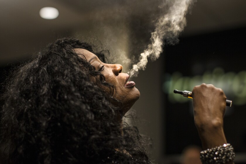 Singer Linda Evans blows vapor from an electronic cigarette.