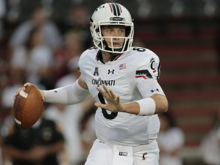Cincinnati quarterback Hayden Moore (8) rolls out of the pocket and looks to throw during the first half of an NCAA college football game against Tennessee-Martin, Thursday, Sept. 1, 2016, at Nippert Stadium in Cincinnati. (Kareem Elgazzar/The Cincinnati Enquirer via AP)