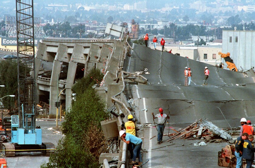 Workers check the damage to Interstate 880 in Oakland after it collapsed during the Loma Prieta earthquake in 1989.