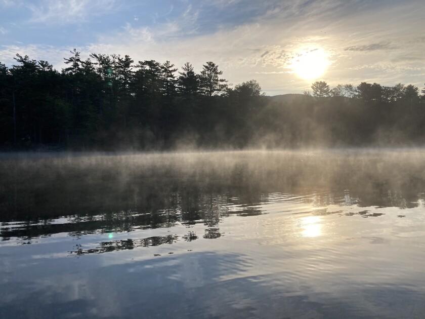 Mist rises off of Lake Megunticook, Maine.