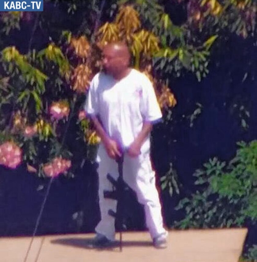 In this frame from video provided by KABC-TV in Los Angeles, a wanted man armed with a rifle stands on the roof of a San Fernando Valley home after a freeway chase Monday, June 9, 2014, in the North Hollywood area of Los Angeles. Authorities shut down nearby freeway on-ramps, locked down schools and evacuated at least one as police waited him out. (AP Photo/KABC-TV) USE ONLY WITH KABC LOGO